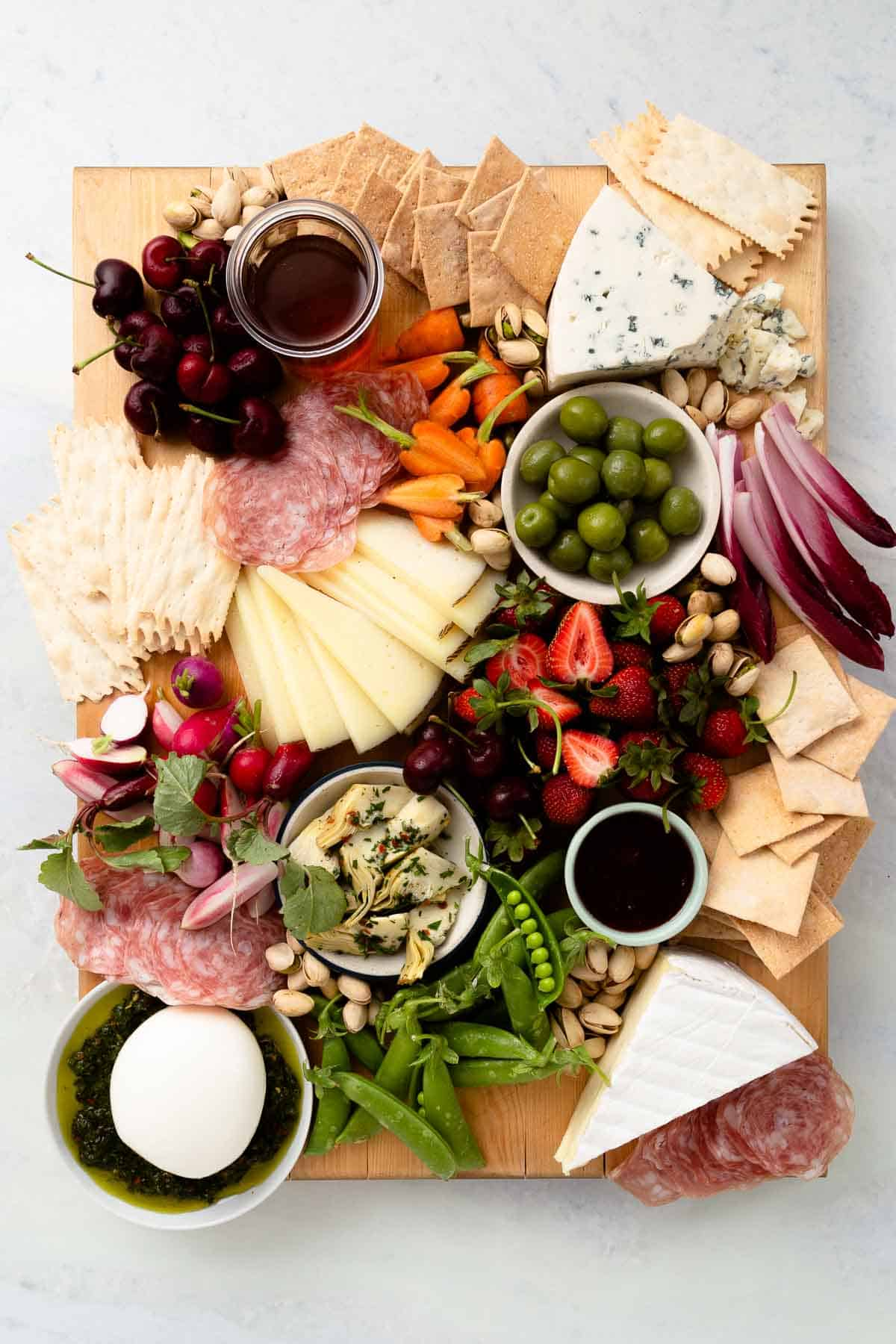overhead view of a packed snack board with cheese, meat, crackers, and fruit