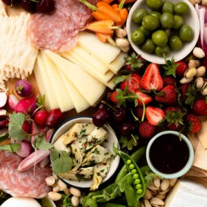 close up on a snack board filled with cheese, meat, green olives, and fruit