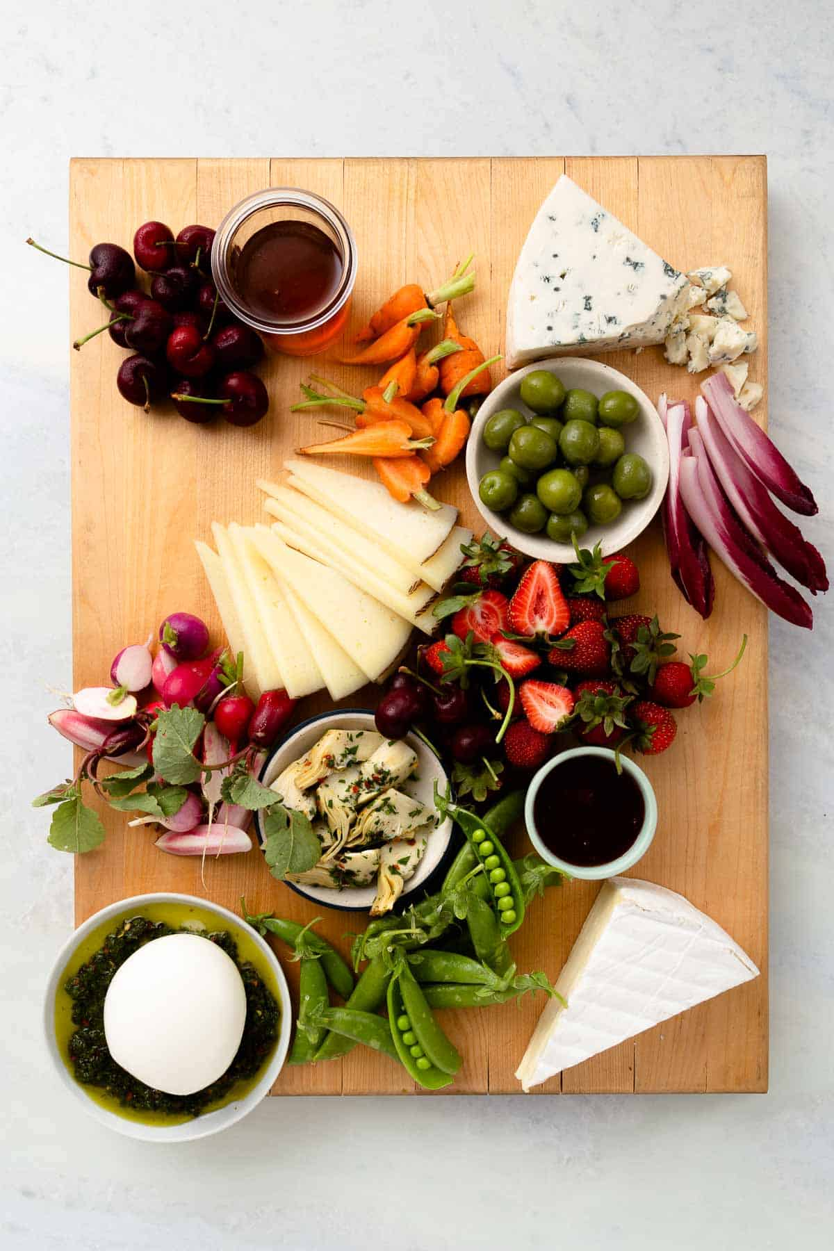 filling a large wood board with vegetables, green olives, jam, and white cheeses