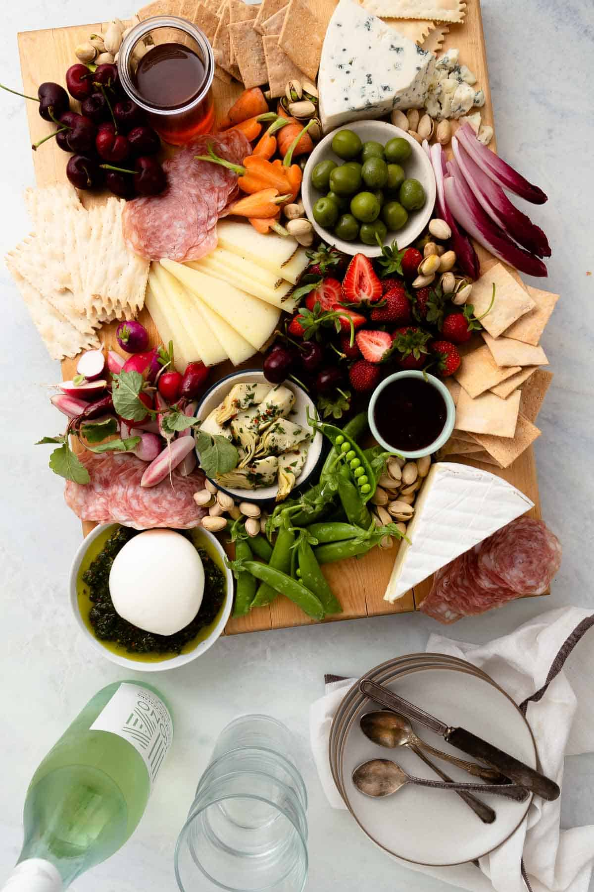 large wood board filled with crackers, cheese, meat, vegetables, and fruit