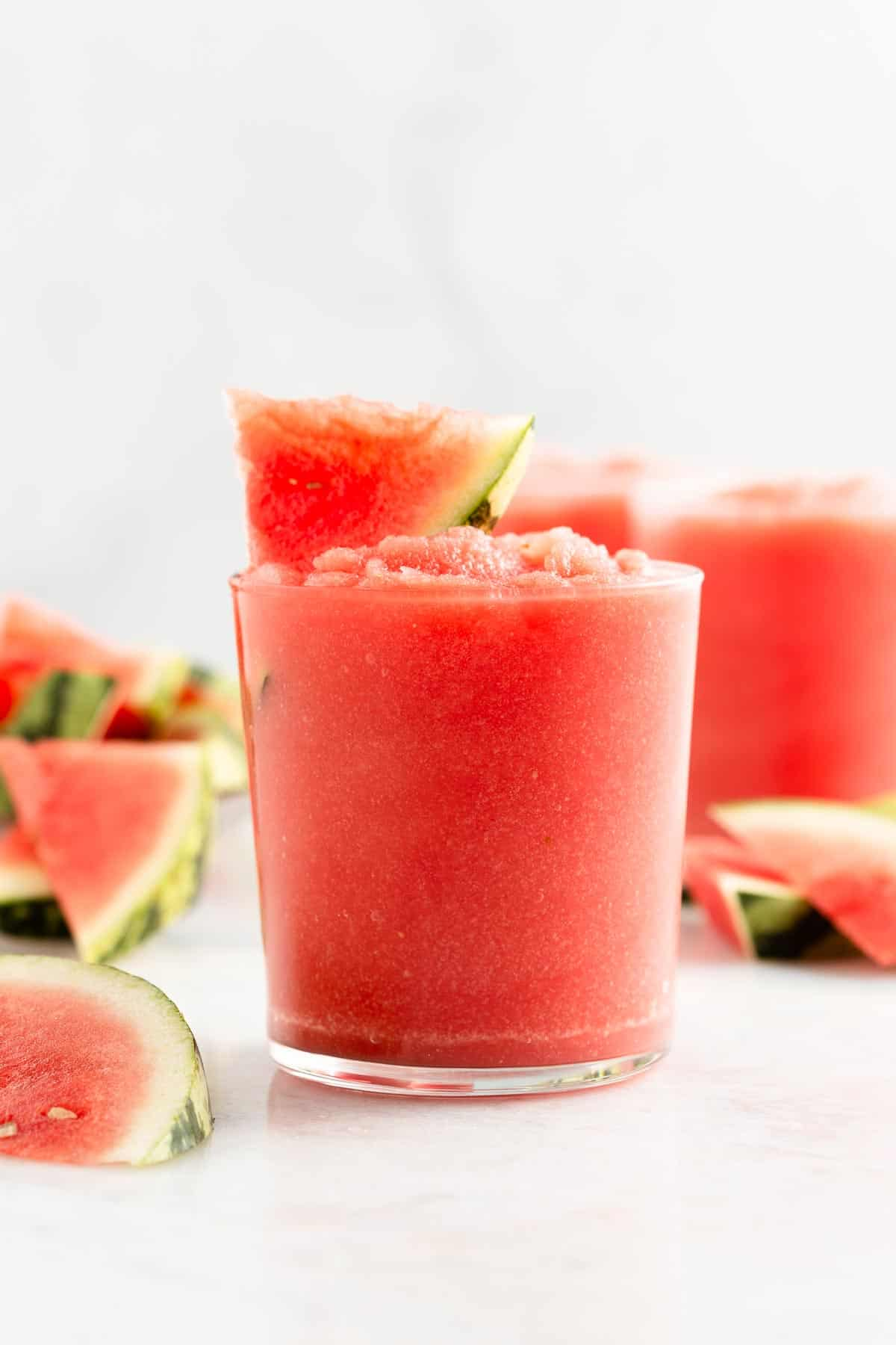 pink slushy drink garnished with a watermelon slice