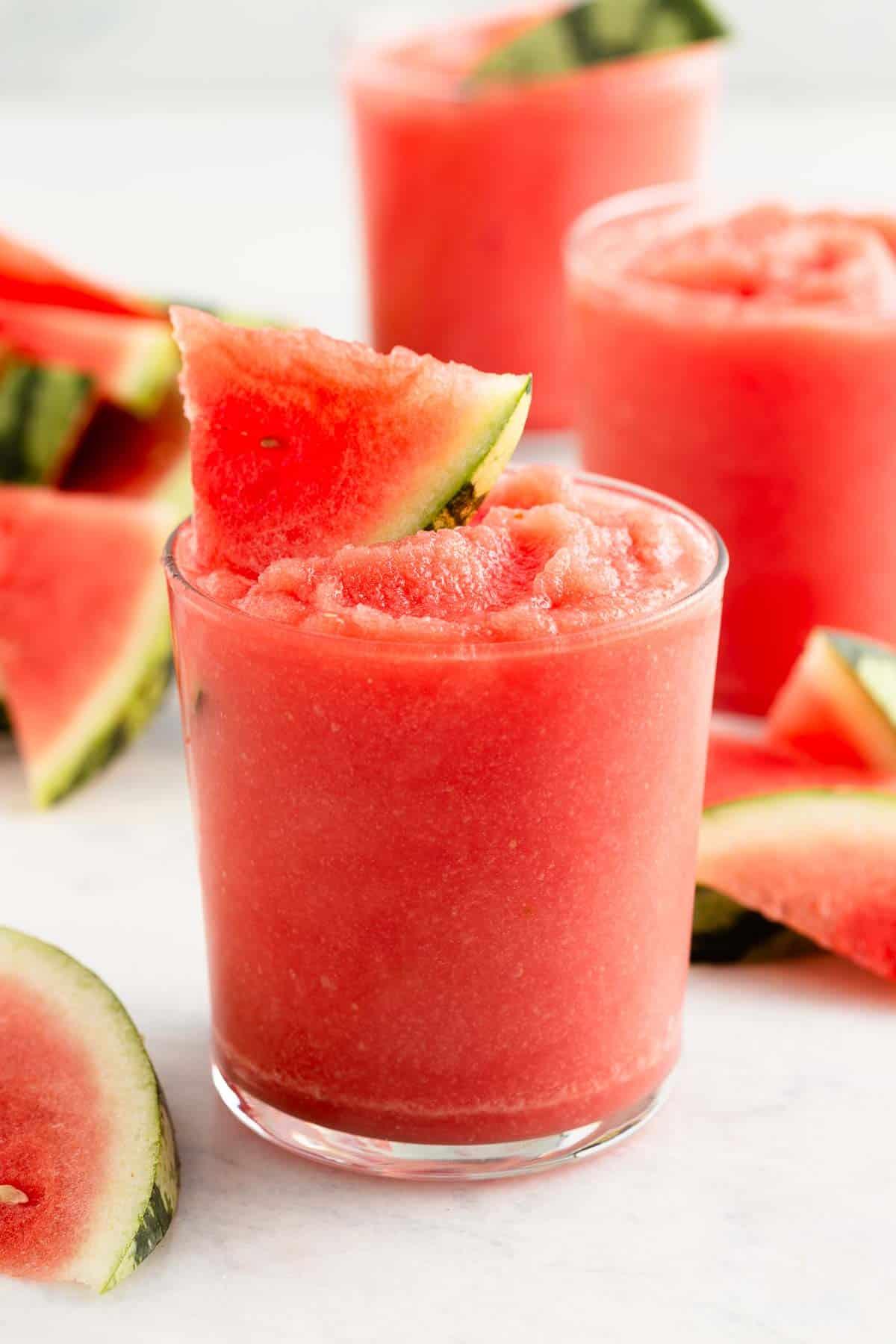 close up on a pink slushy drink garnished with a watermelon slice