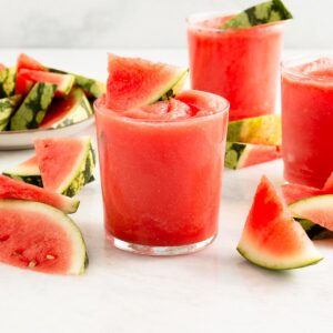 3 pink slushy drinks surrounded by slices of watermelon