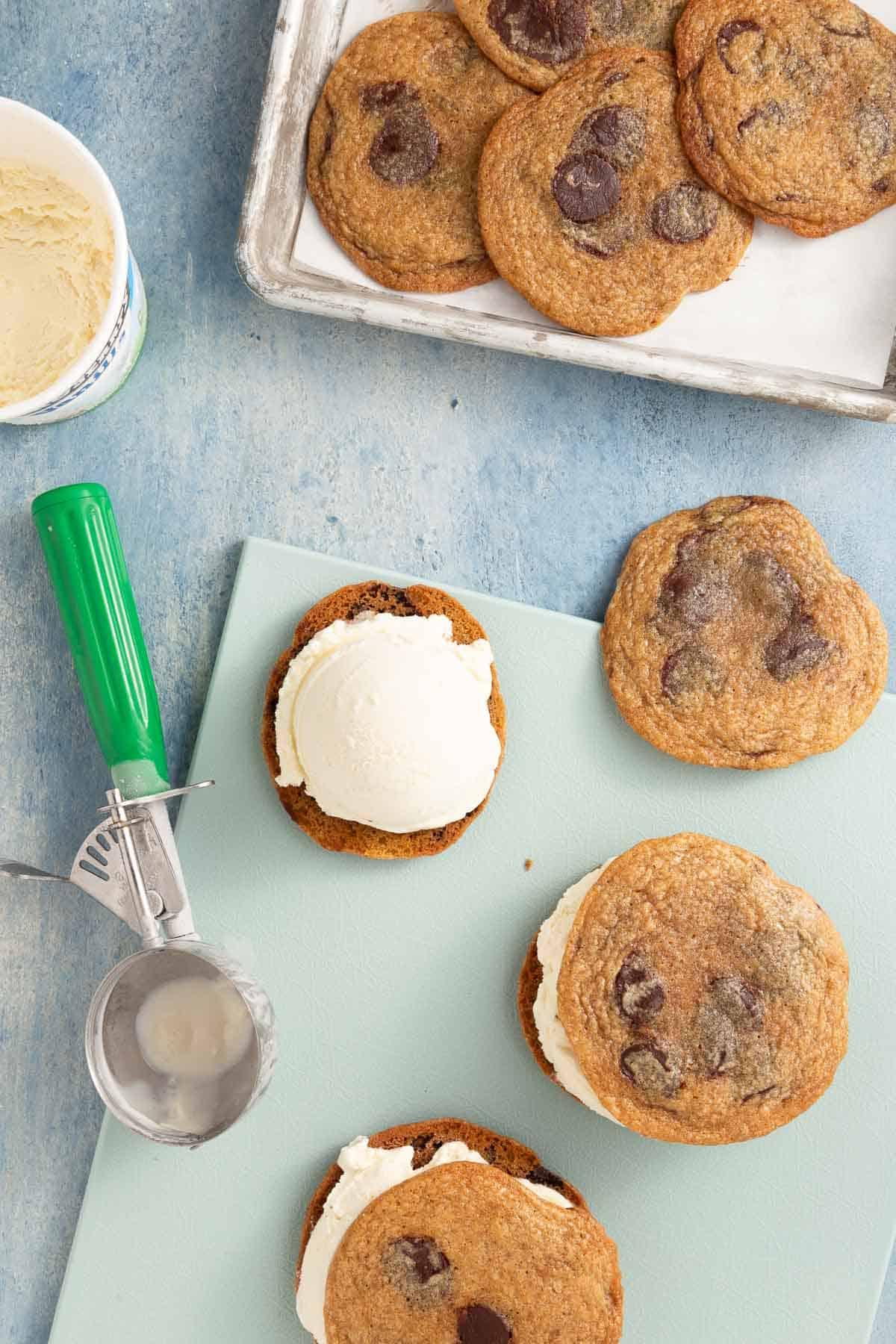 scooping vanilla ice cream onto chocolate chip cookies