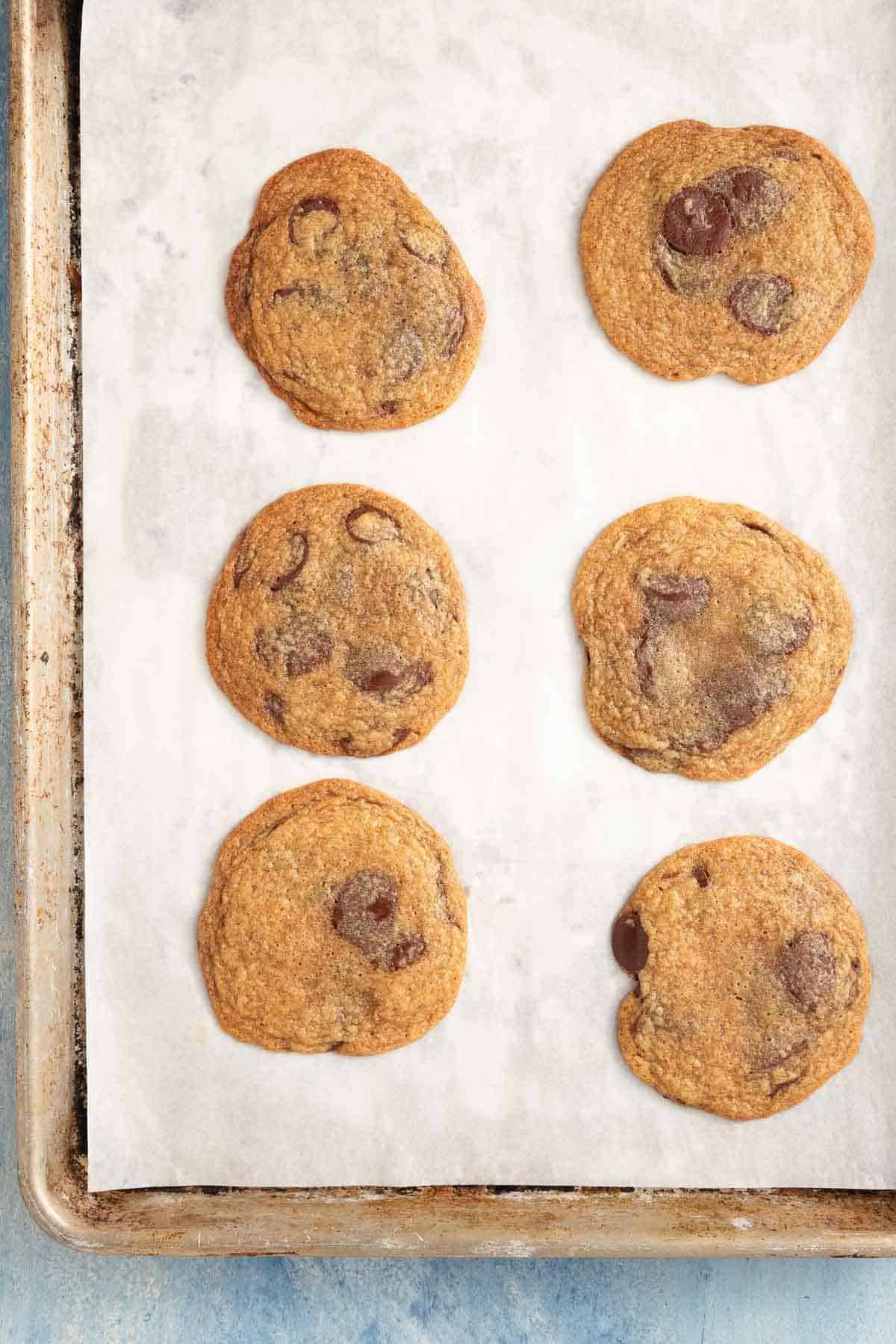 baked chocolate chip cookies on a parchment lined baking sheet