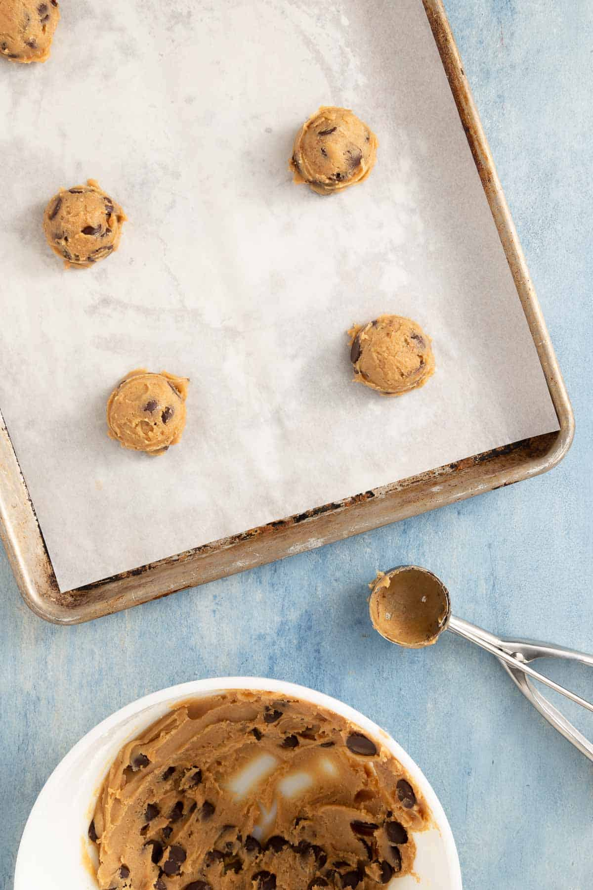 using a cookie scoop to scoop cookie batter from a bowl onto a baking sheet