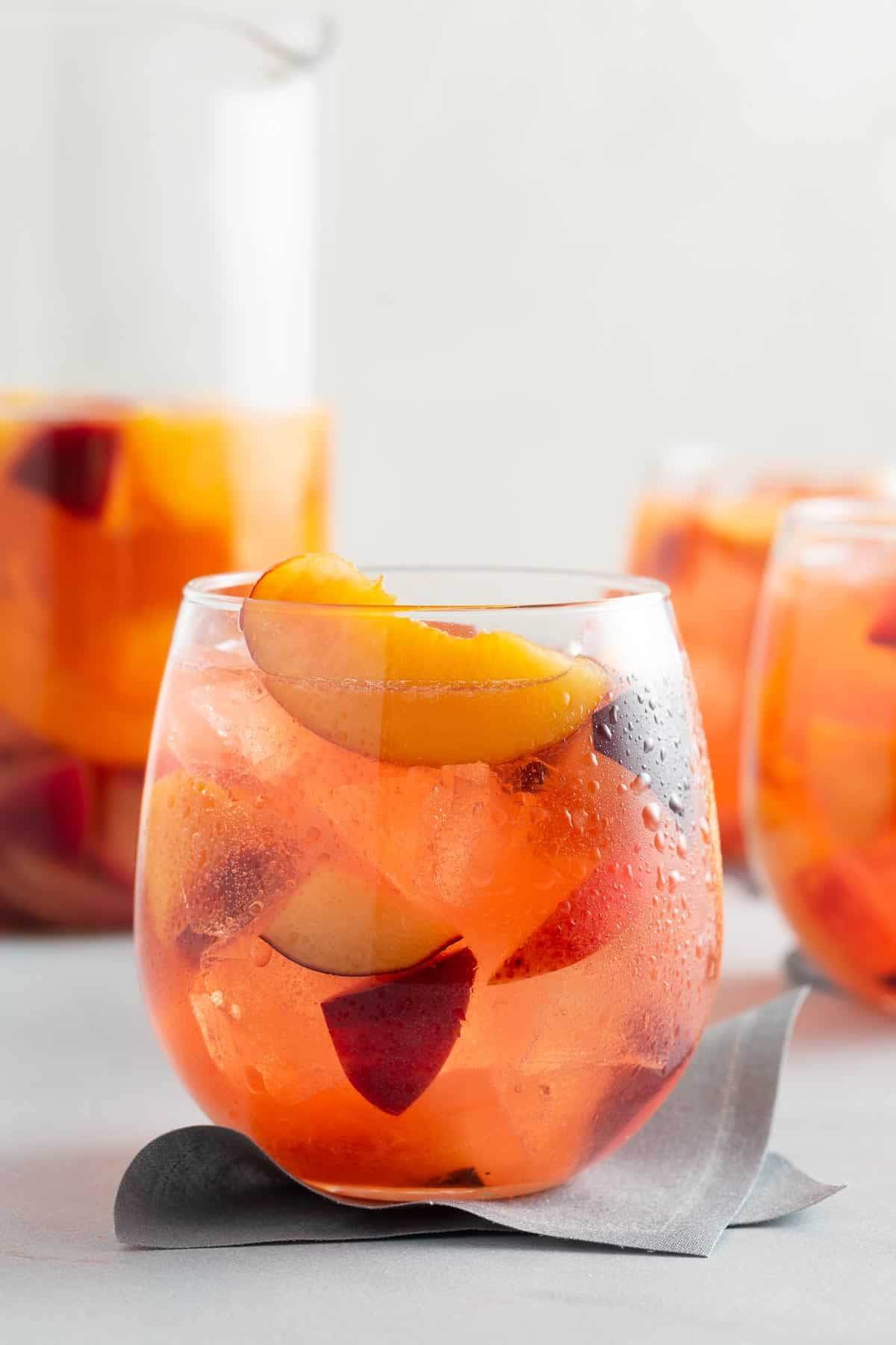 close up on a glass of pink punch with chunks of fruit