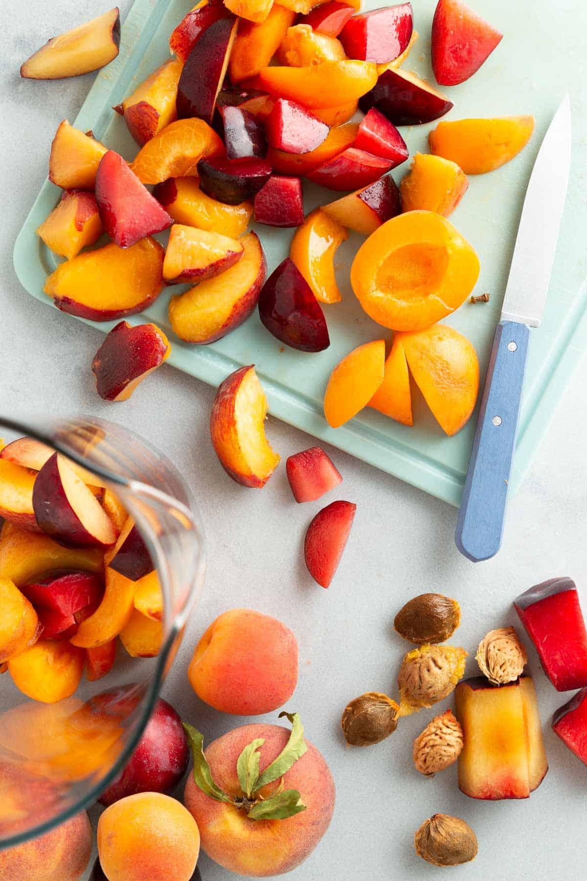 Cutting peaches on a teal cutting board