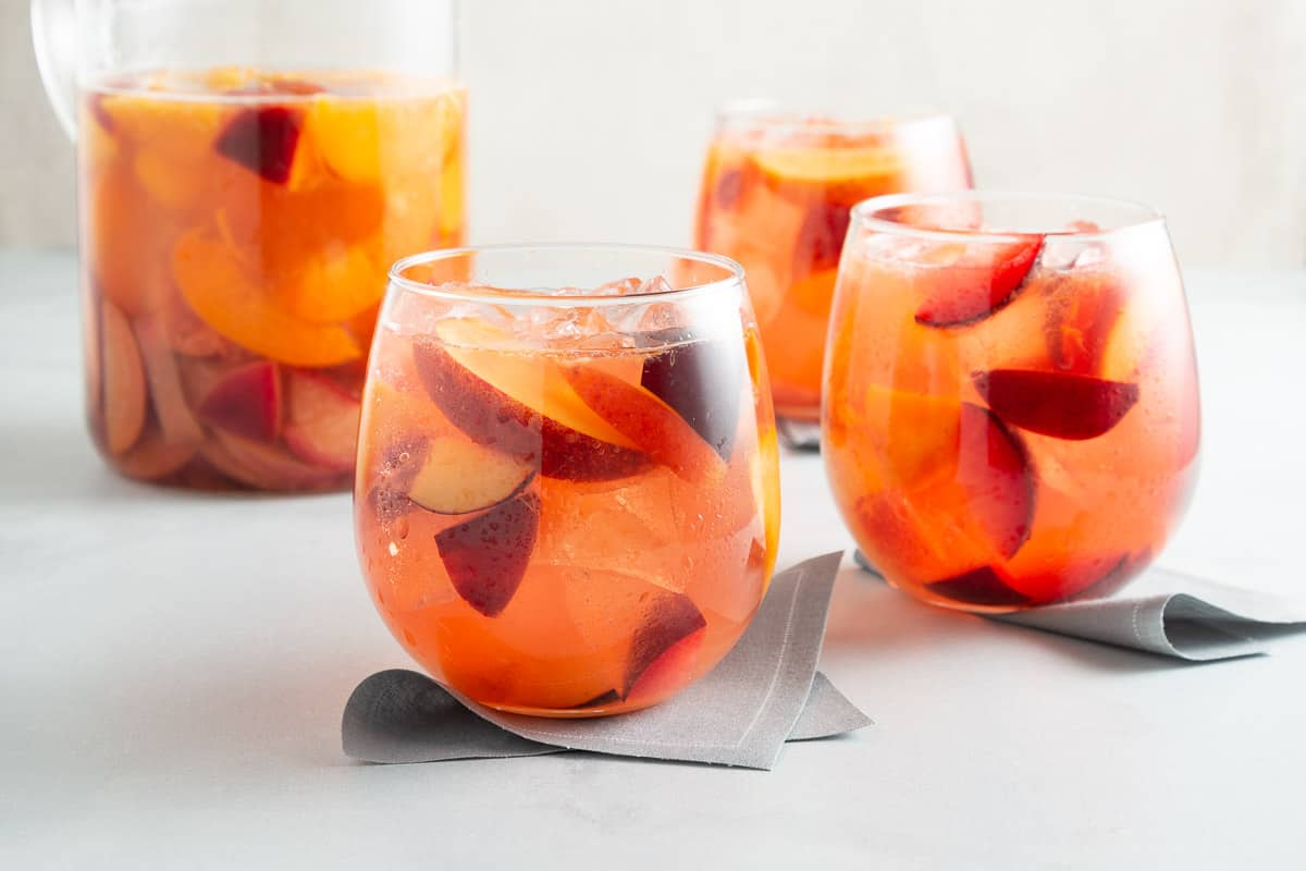 pink punch with chunks of fruit and ice in stemless wine glasses