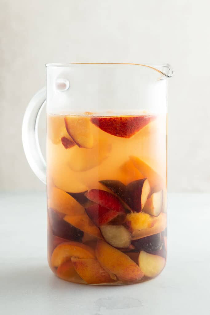 chunks of fruit and liquid in a large glass pitcher