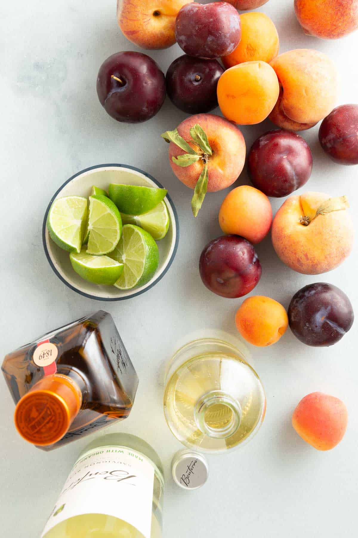 overhead view of peaches, plumbs, and limes next to bottles of liquor