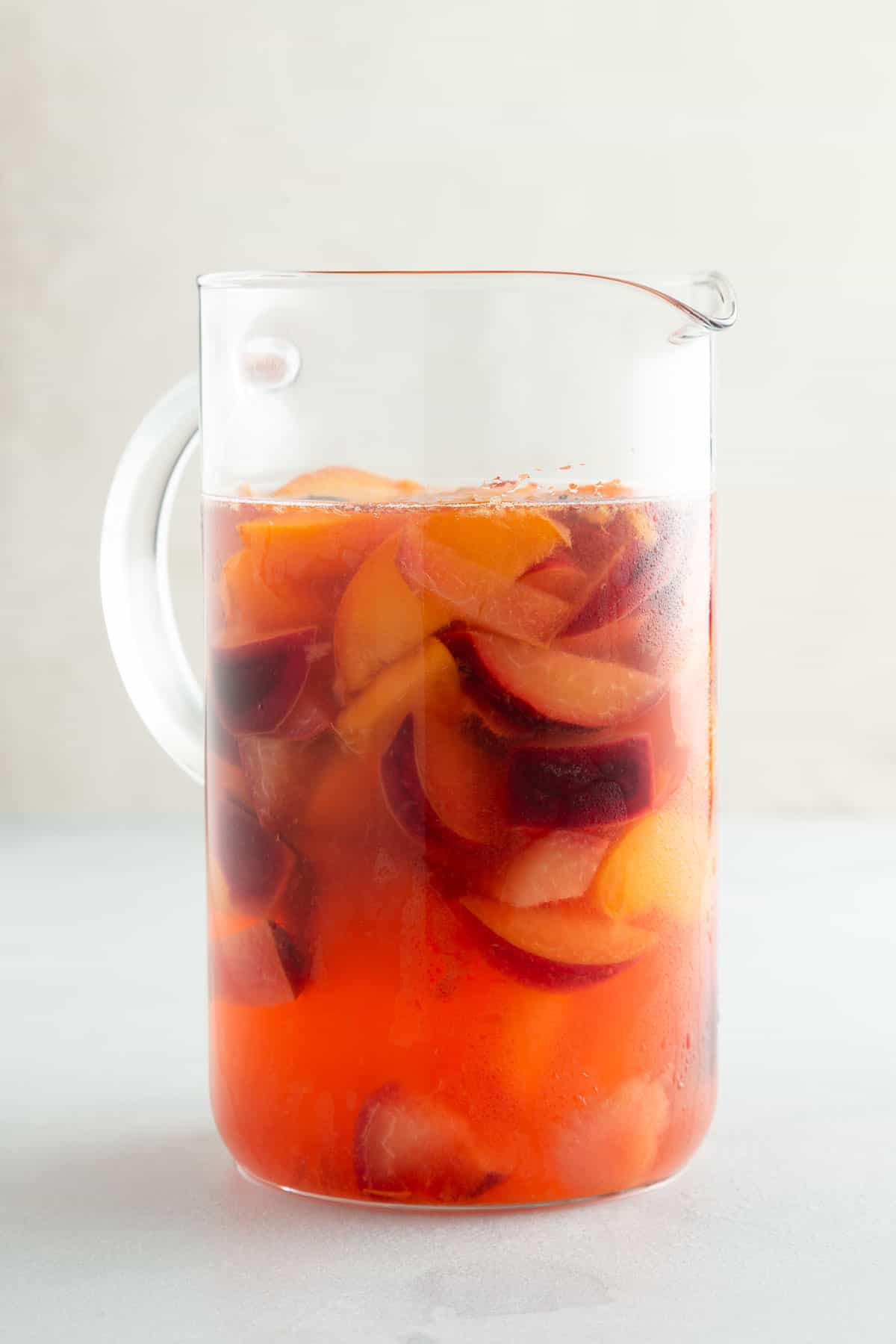 pink punch and fruit slices in a large glass pitcher