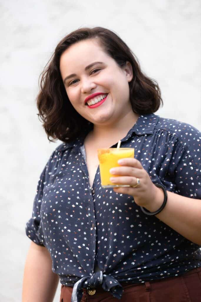 woman with brown hair wearing a blue button up shirt smiling and holding a frozen mango margarita