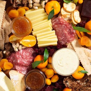 winter citrus, salami, sliced cheese, and crackers on a wooden cutting board